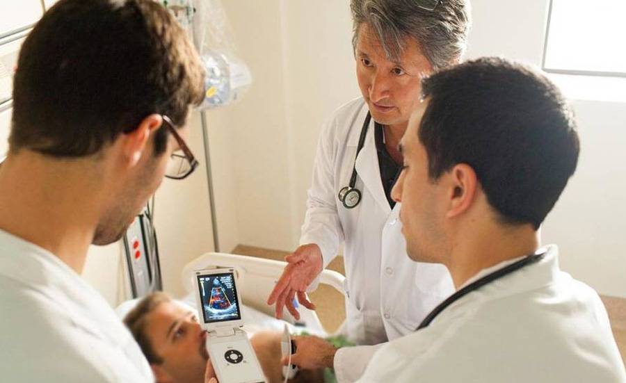 A group of doctors train on a new device.
